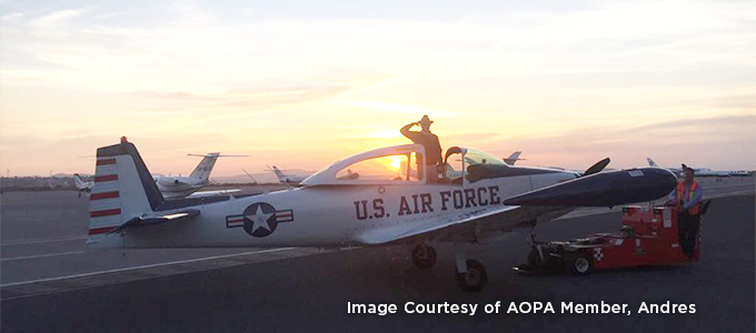 "Image Courtesy of AOPA Member Andres. Image of aircraft with ""U.S. Air Force"" on the side and sunset in the background. Man in aircraft saluting towards camera."