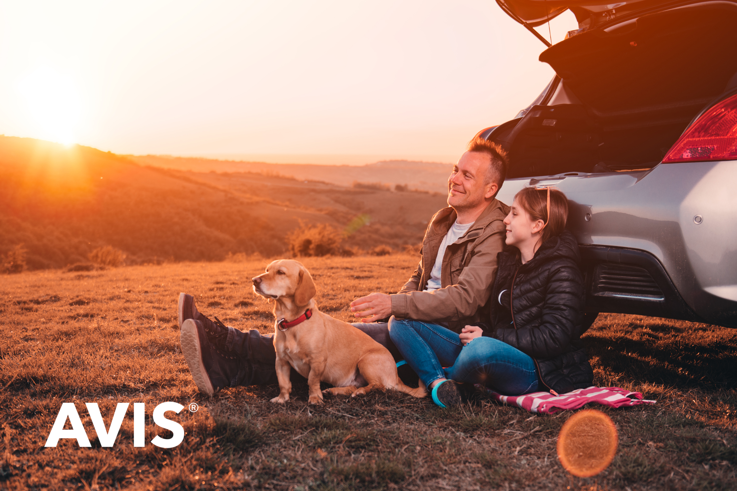 People sitting by car with dog. AVIS logo in bottom left-hand corner.